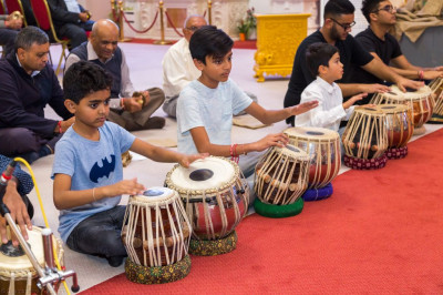 Young disciples perform tabla and various other percussion insturments as devotional songs are performed to please the Lord