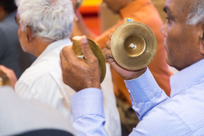 The older members of the congregation play traditional hand cymbals accompanying the performance of devotional songs