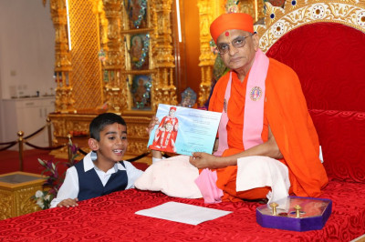 His Divine Holiness Acharya Swamishree blesses a young disciple for his achievement in Swamibapa Gujarati School