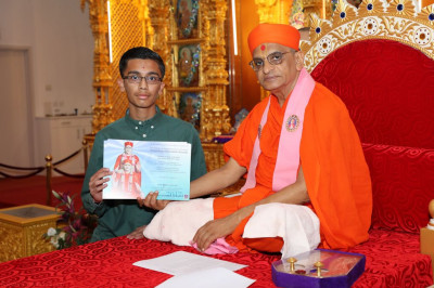 His Divine Holiness Acharya Swamishree blesses a young disciple for achieving a pass in Gujarati GCSE
