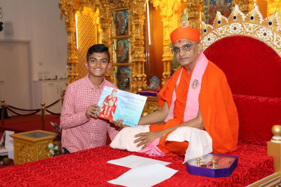 His Holiness Acharya Swamishree presents an achievement award to the young disciple for passing Sanskar Deepika part 2