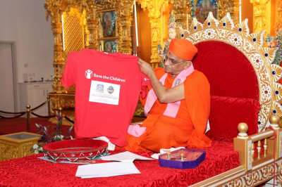 His Divine Holiness Acharya Swamishree officially unveils the new t-shirt to be worn in the Spetember 9th 2017 10-mile walk to raise money for Save the Children