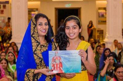 A young disciple is presented with an achievement award for taking part in the preparation and performance of the Sadguru Shree Ishwarcharandasji Swami 150th anniversary celebrations presentation