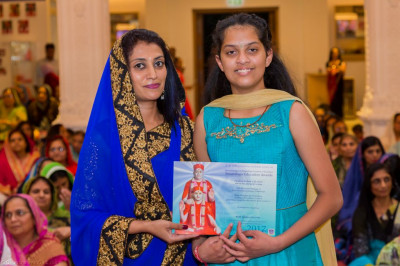 A young disciple is presented with an achievement award for achieving a pass in Sanskar Deepika part 3