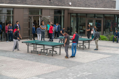 Older disciples play table tennis in the coutyard