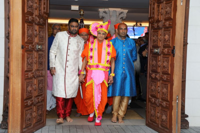 Disciples escort His Divine Holiness Acharya Swamishree out of the mandir hall