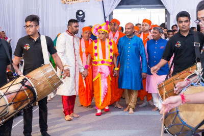 Disciples who have sponsored the celebrations escort His Divine Holiness Acharya Swamishree into Shree Purushottam Mahal as dhol players perform