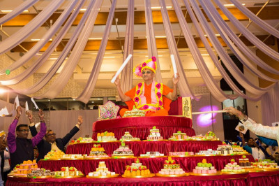 All plates of Indian sweets surround His Divine Holiness Acharya Swamishree