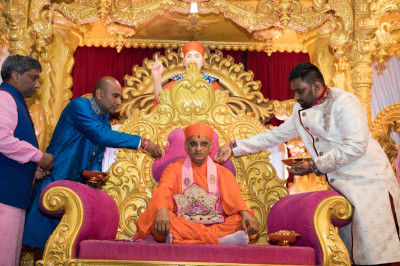 Disciples shower His Divine Holiness Acharya Swamishree and Shree Harikrishna Maharaj with gold flower petals and diamond crystals