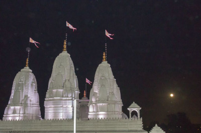The magnificent white towers of Shree Swaminarayan Mandir Kingsbury glistening in the bright white moonlight