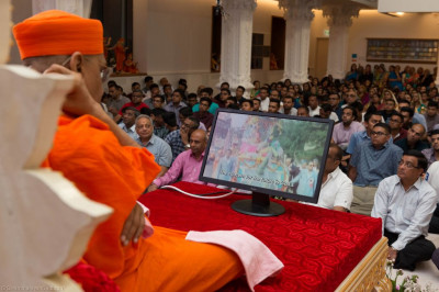 His Divine Holiness Acharya Swamishree watches the video