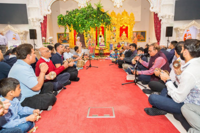 Disciples play hand cymbals and various insturments as they sing devotional songs to please the Lord