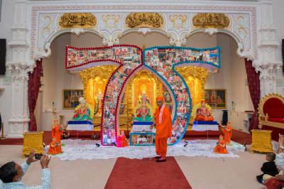 His Divine Holiness Acharya Swamishree swings the Lord seated within the '75' anniversary celebration hindola