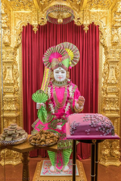 Divine darshan of Lord Shree Swaminarayan dining on delicious cake and sweets and savouries