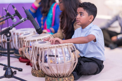 Young disciples perform tabla compositions to please the Lord