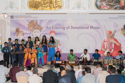 Young disciples perform a devotional song with harmonium and tabla