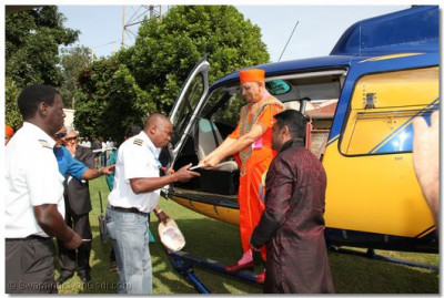 His Divine Holiness Acharya Swamishree presents maha-prasad to the helicopter pilot