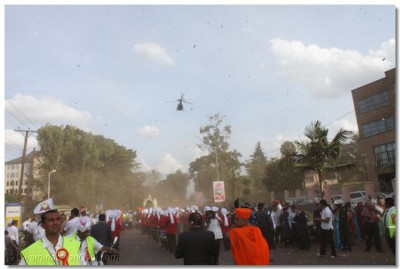 The procession proceeds through the city as the helicopter continuously showers fresh fragrant flower petals from overhead