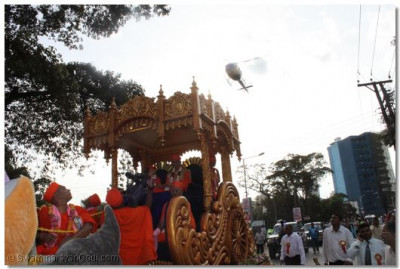 Divine darshan of Shree Muktajeevan Swamibapa and His Divine Holiness Acharya Swamishree seated on the magnificant chariot with Sants, as the helicopter flies overhead and showers fresh fragrant rose petals over the procession