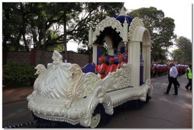 Divine darshan of Lord Swaminarayan and Shree Muktajeevan Swamibapa seated with Sants on the intricatally decorated chariot