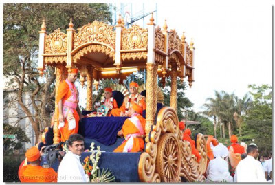 His Divine Holiness Acharya Swamishree blesses disciples and onlookers from the rear of the magnificant chariot during the procession