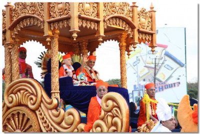 His Divine Holiness Acharya Swamishree blesses disciples and onlookers seated on the magnificant chariot during the procession