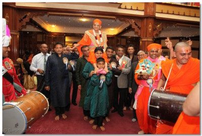 His Divine Holiness Acharya Swamishree is carried by disciples as Sants and disciples play Dhol