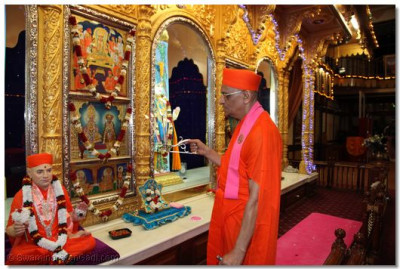 His Divine Holiness Acharya Swamishree performs aarti to Lord Swaminayan, Shree Abji Bapashree, and Shree Muktajeevan Swamibapa