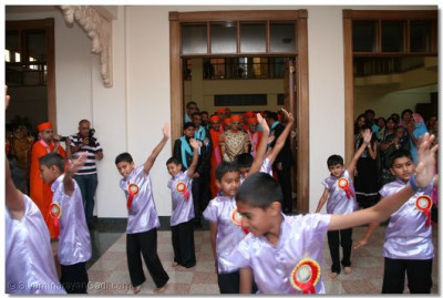Young disciples dance to a devotional song at the entrance of H.H. Swamibapa Hall