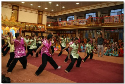 Young disciples continue to perform an energetic dance welcoming His Divine Holiness Acharya Swamishree into the temple