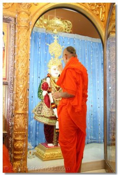 His Divine Holiness Acharya Swamishree applies chandlo to all the murtis in the sinhasan during the Patotsav ceremony