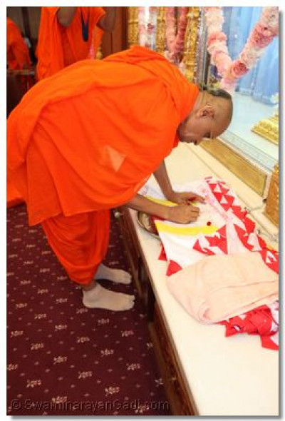 His Divine Holiness Acharya Swamishree blesses the flag that will be raised outside the temple