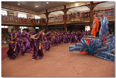 Disciples perform an energetic dance as His Divine Holiness Acharya Swamishree stands on the magnificant chariot