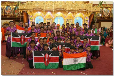 The national flags of Kenya and India are upheld as His Divine Holiness Acharya Swamishree gives darshan with all of the dancers that took part in the closing ceremony