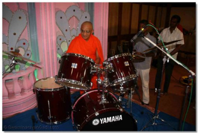 Acharya Swamishree plays the drum set before the start of the performances