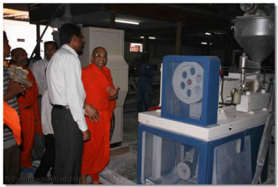 Acharya Swamishree is given a tour of the factory