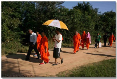 Acharya Swamishree, sants and disciples walk to the river boat