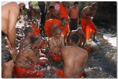 Acharya Swamishree and sants bathe in the river