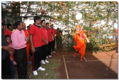 Acharya Swamishree hits the serve at Volleyball
