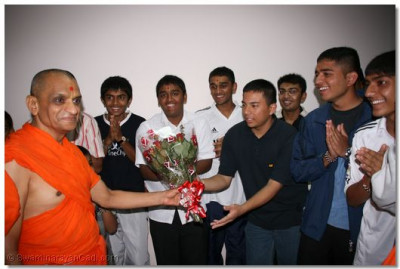 Young devotees offering Acharya Swamishree with a bouquet of love