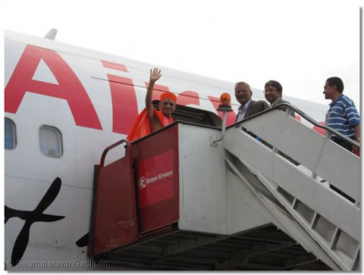 Acharya Swamishree waves to devotees whilst boarding the aircraft