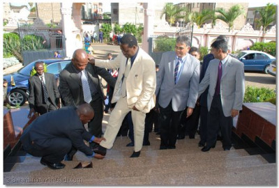 His security details assist him with removing his shoes to enter the temple