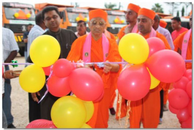 Acharya Swamishree cuts a ribbon for a new truck yard