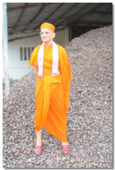 H.D.H Acharya Swamishree standing on a heap of iron ore