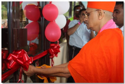 Acharya swamishree cutting the ribbon of a new office block