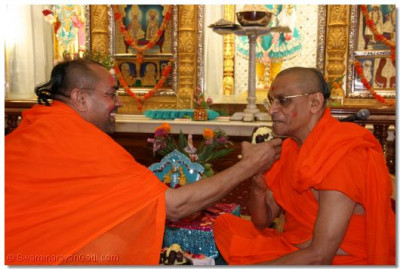 Sants take the opportunity of offering Acharya Swamishree with ghee and dates