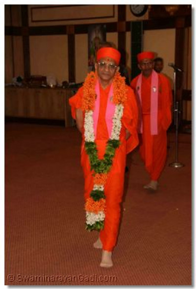 Acharya Swamishree with a garland similar in colour to the Indian National Flag