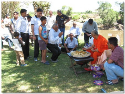 Acharya Swamishree gives prasad to devotees