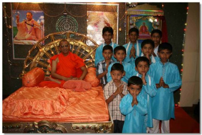 Young devotees being blessed by Acharya Swamishree for their exemplary performance while reciting the Kirtan