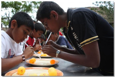 Young devotees take part in straw and ball game